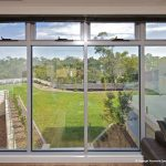 Glass windows overlooking green lawn